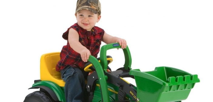 Little boy riding a Peg Perego John Deere Mini Tractor Loader ride on tractor toy.
